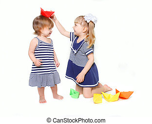 two young sisters in sailor dresses with paper ships over white