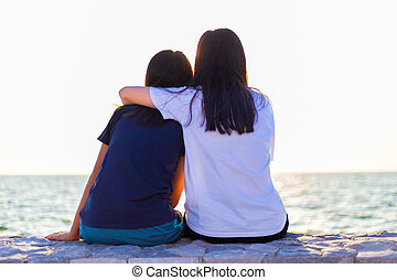 Two young sisters sitting on stone wall watching sunset over the ocean