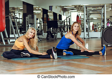 two young slender blond women doing exercises in gym