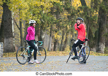 Two Young Smiling Female Cyclists with Road Bicycles Resting and in Park in Cold Autumn Day. Healthy Lifestyle.