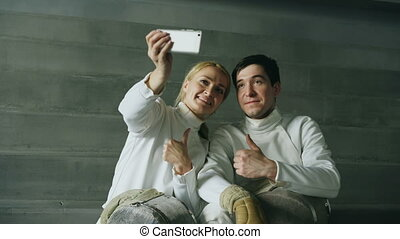 Two young smiling fencers man and woman taking self portrait on smartphone camera after fencing training indoors