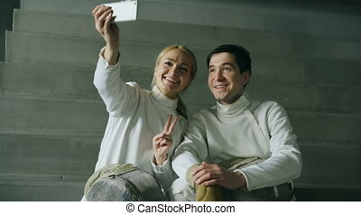 Two young smiling fencers man and woman taking selfie on smartphone camera after fencing training indoors