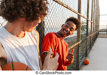 Two young smiling multiethnic men basketball players ...