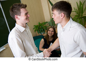 Two young smiling the person shake each other hands
