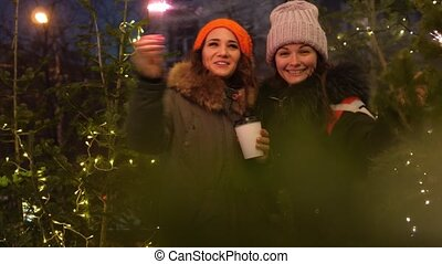Two young smiling women holding burning sparkler and coffee in cold winter evening on street. Glowing blurred bokeh lights of Christmas