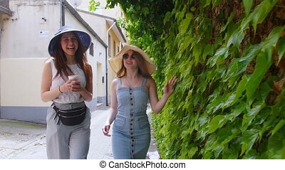 Two young smiling women walking in panamas on the streets...