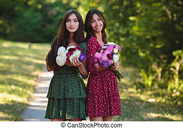 Two young smiling women with flowers