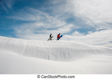 Two young snowboarders standing on the hill with the snowboards