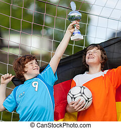 two young soccer players celebrating with trophy