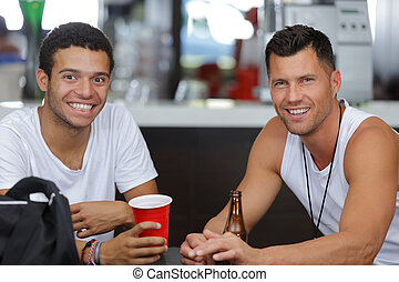 two young sporty men having a drink in a bar