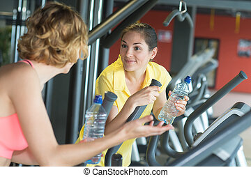 two young sporty women run on machine in the gym