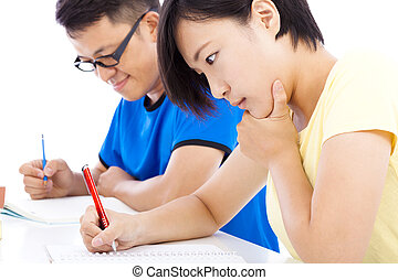 two young students exams together in classroom