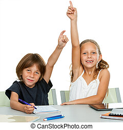 Two young students raising hands at desk. - Portrait of two ...