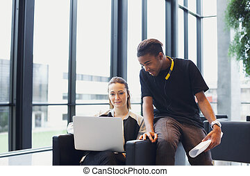 Two young students using laptop in campus