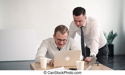 Two young successful businessmen work in the office, look at laptop on the table. discuss business