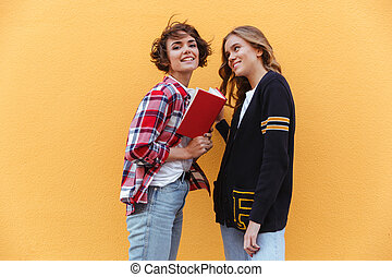 Two young teenage girls with books outdoors