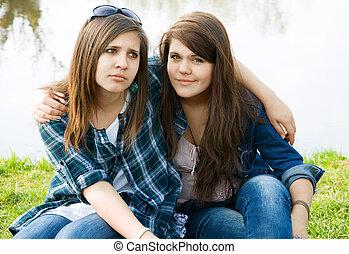 Two young teens feel sad on the lake