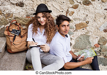 Two beautiful young tourists with smartphone, map and camera in the old town. Teenagers sitting on stairs, writting..