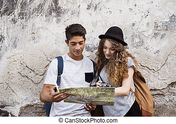 Two young tourists with a map in the old town. - Two...