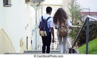 Two young tourists with backpacks in the old town.