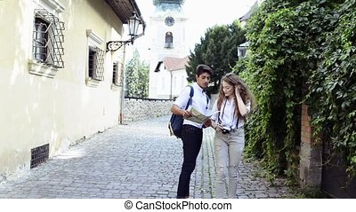 Two young tourists with map and camera in the old town. -...