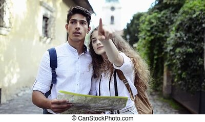 Two young tourists with map in the old town.