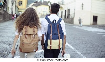 Two young tourists with map in the old town. - Two beautiful...
