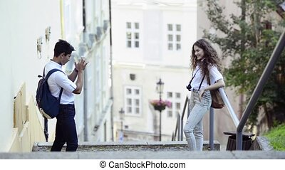 Two young tourists with smartphone and camera. - Two...