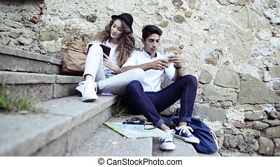 Two young tourists with smartphone in the old town.