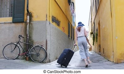 Two young traveling happy women walking with a luggage on...