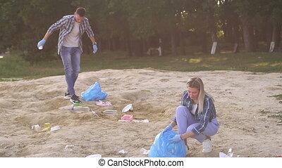 Two young volunteer gathering garbage on river bank. Volunteer concept.