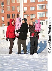 two young woman and grandfather with children on the walk in the winter 2