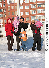 two young woman and grandfather with children .winter.