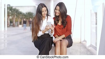 Two young woman checking a text message - Two stylish young...