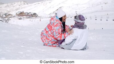 Two young woman enjoying a frolic in the snow