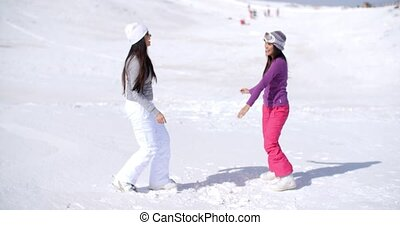 Two young woman frolicking in winter snow
