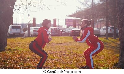 Two young woman in sport costumes doing squats in park