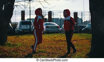 Two young woman in sport costumes freezing in park. Mid shot