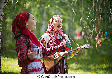 Two young woman in traditional russian clothes singing in the forest. One of them playing balalaika - gorizontal shot