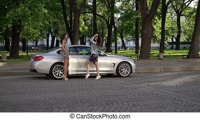 Two young woman posing near luxury sports car in a city