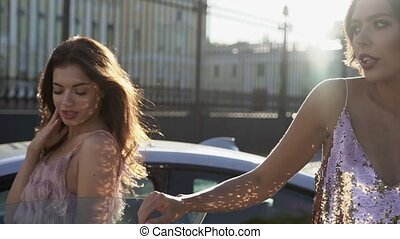 Two young woman posing near luxury sports car