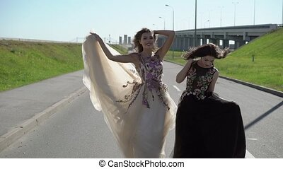 Two young woman posing on a road