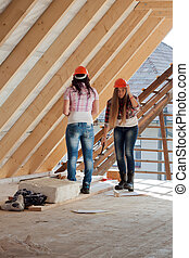 Two young woman repairing the roof of the house