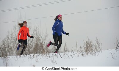 Two young woman running technically in winter outdoor