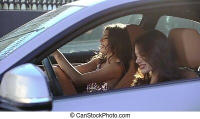 Two young woman sitting in luxury sports car in a city