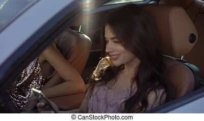 Two young woman sitting in luxury sports car