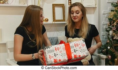 Two young woman sitting on the couch holding a big holiday...