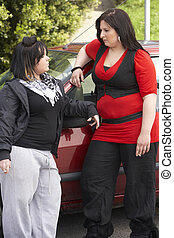 Two Young Woman Standing Next To Car