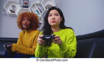 Two young woman using joystick controller playing video game on. Competition win and loss. High quality 4k footage