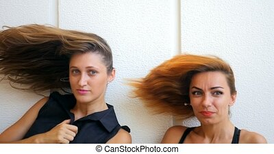 Two young woman with flying hair